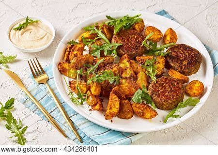 Vegan Lentil And Bean Burgers Patties With Baked Potato Wedges,  Rocket Leaves And Hummus On A White