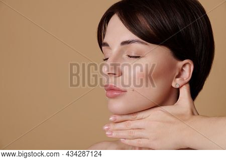 Close-up Beauty Portrait Of Brunette Woman With Closed Eyes Doing A Lifting Rejuvenating Massage On