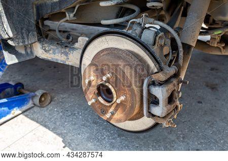 Worn Rusty Car Brake Disk. Repairing Brakes On Car. Car Brake Disc Close Up. Car On Pneumatic Jack