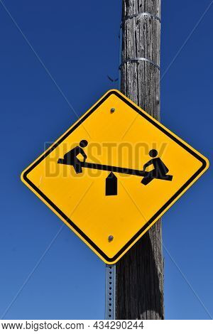 A Playground Sign Attached To A Utility Pole Indicates A Playground For Children Ahead.
