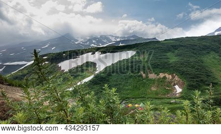 There Are Bright Tents Of A Tourist Camp In The Valley. There Is Green Vegetation On The Mountainsid