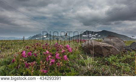 A Picturesque Mountain Range Against A Cloudy Sky. Snow On The Slopes. A Green Meadow In The Valley.