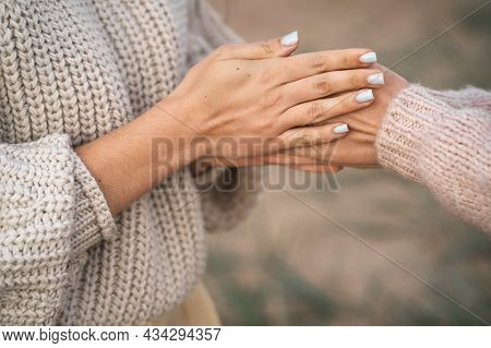 The Girls Are Frozen For Walks And Warming Their Hands. A Friend Warms Her Hands. Close-up Of The Ha
