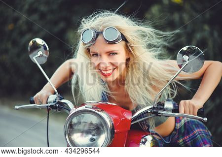 The Biker Is A Beautiful Cheerful Girl Sitting On Her Motorcycle, A Little Crazy. Wear Short Shorts