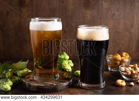 Different Sorts Of Craft Beer In Frosty Glasses And Snacks On A Dark Rustic Table. Beer Brewery Conc