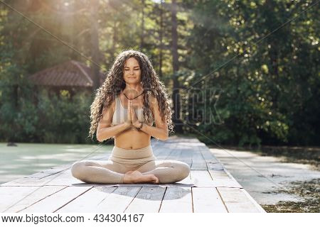 A Woman Practicing Yoga, Sitting On A Mat In A Lotus Position, Meditates On A Wooden Bridge Near A P
