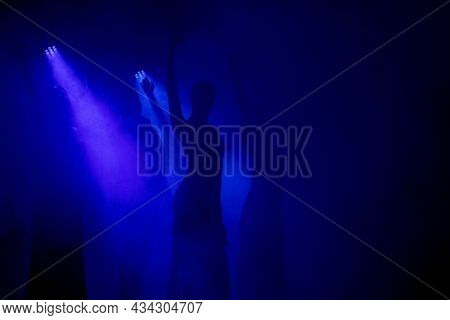 Spanish Flamenco Dancer Silhouette Over Dark Blue Background. Space For Your Design.