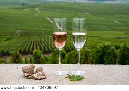 Glasses Of White And Rose Brut Champagne Wine, Firestones From Vineyards Soil And View On Grand Cru