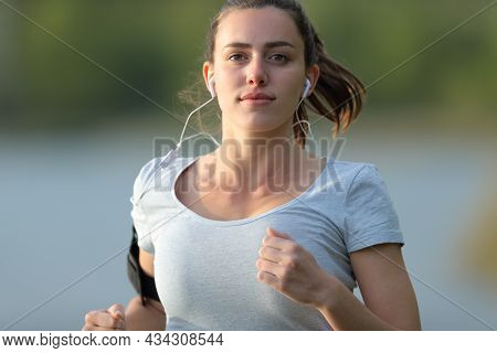 Front View Portrait Of A Runner Running With Earbuds In A Lake