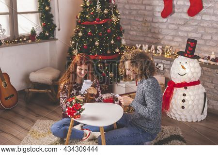 Beautiful Young Couple In Love Having Fun At Home On Christmas Day, Making Christmas Decorations Out