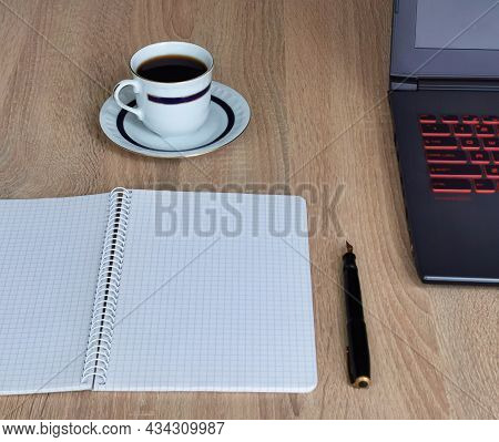 Close Up Cup Of Coffee, Laptop Computer, Notebook And Pen On Wooden Desk Office. Workplace At Home