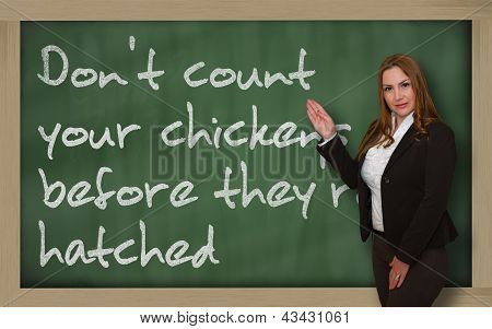 Teacher Showing Don't Count Your Chickens Before They're Hatched On Blackboard