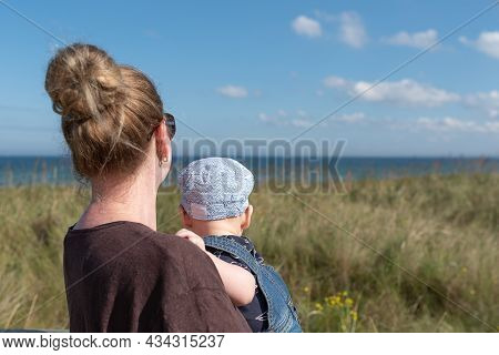 Mother Carrying Baby Boy Looking At The Sea