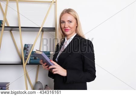 Attractive Blonde Business Woman In Business Suit Stands At Bookshelf And Chooses A Book To Read. Wo