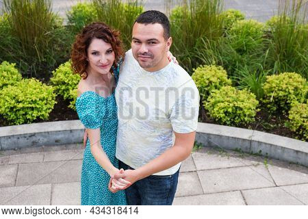 Couple In Love Dancing In The Park Turned Around And Looked At The Camera. Man In T-shirt And A Curl