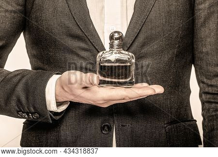 Man In A Suit Holding A Bottle Of Perfume Isolated On White Background. Perfume Or Cologne Bottle An