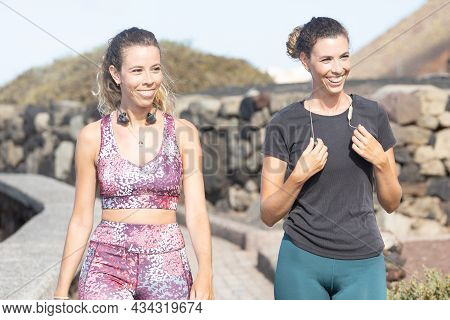 Women Laugh As They Walk. Young Blonde Sisters Laugh As They Share An Afternoon Of Exercise On A Sun