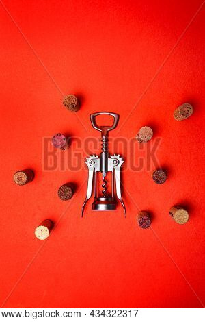Metal Corkscrew With Wine Corks On A Red Background