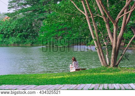 Back View Of Asian Woman With Artificial Bouquet Sit To Relax Near Pond In Garden. Summer Vacation I