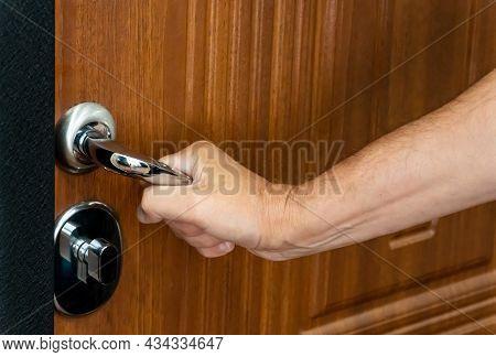 A Naked Hand Pressing Down On The Metal Handle Of The Door Lock Of A Closed Door. Opening The Door