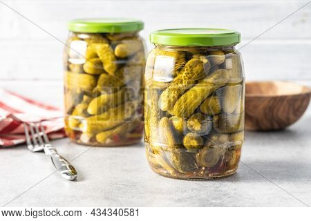 Small pickles. Marinated pickled cucumbers in jar on kitchen table.