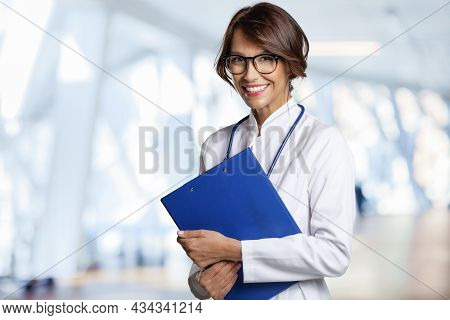 Smiling Female Doctor Standing At Hospital Corridor While Looking At Camera And Smiling