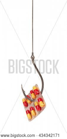 Fishing hook with pill bait isolated on white background. Drugs catching people concept. Prepared decoy for being hooked on drug pharmacy medicament addiction