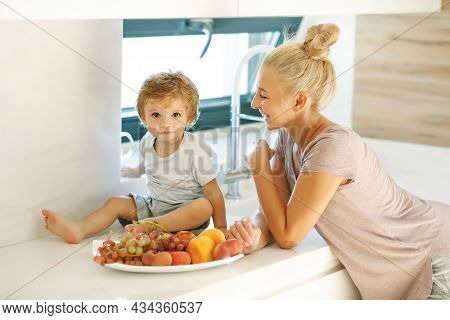 Mom Feeds The Baby. Young Woman Feeds Her Baby In The Kitchen. High Quality Photo