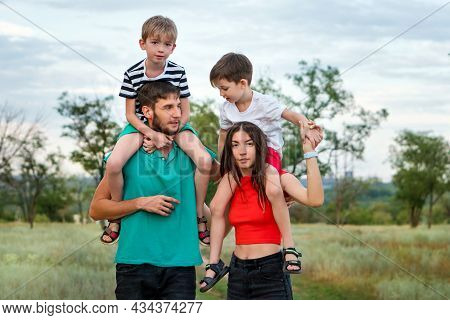 Young Happy Authentic Family On Walk In Rural Settings In Summer Day. Parents Keep Their Sons Around