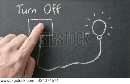 Man's Finger On Drawing Of Power Outlet That Connects Power To Light Bulb On Blackboard With Words,