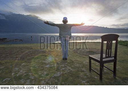 Woman Standing Alone On The Ground, Hands Raise With Open Arms Against Light Blue Nature Lake View I