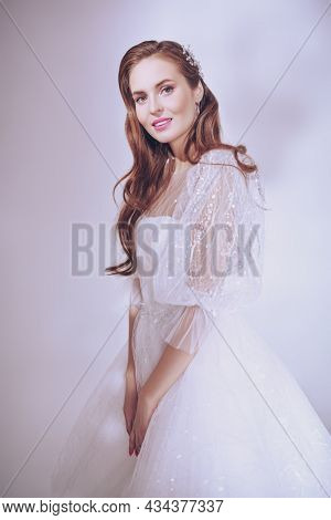 Portrait of a beautiful smiling bride lady in a couture white wedding dress. Wedding style. Wedding make-up and hairstyle.