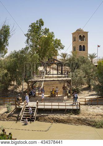 Bethany, Jordan - September 26th, 2021: Pilgrims Immerse Themselves In The Jordan River Guraded By A