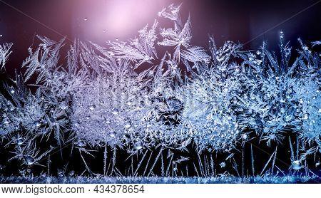 Frozen winter window. Window frozen glass, ice crystals. Snow frame. Beautiful Hoarfrost pattern, rime on black background. Christmas or New Year backdrop.