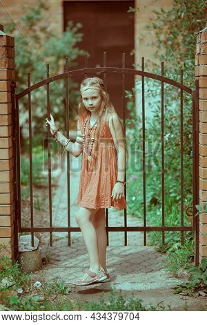 Full length portrait of a cute girl child dressed in hippie style standing at the gate in a summer park. Romantic hippie style.