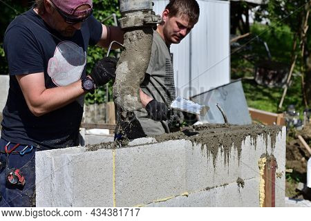 A Combination Of Handwork By A Mason And A Concrete Pump While Placing Concrete In Walls