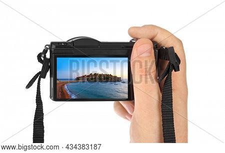 Hand with camera and Island Sveti Stefan - Montenegro image (my photo) isolated on white background
