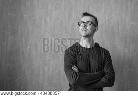 Caucasian Man In Glasses Looking Up And Standing With Folded Arms On Gray Background. Monochrome Por