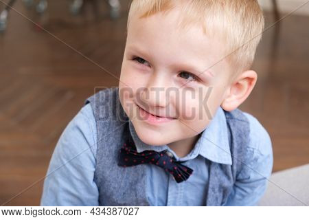 Portrait Of A Five-year-old Blonde Boy In A Shirt, Vest And Bow Tie