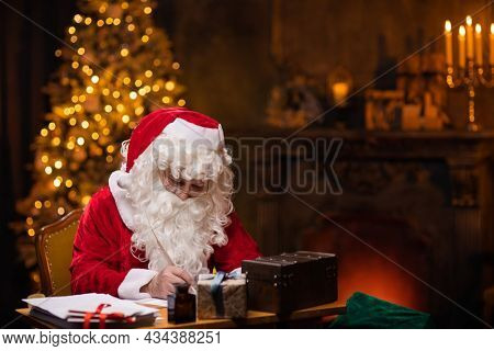 Workplace of Santa Claus. Cheerful Santa is writing the letter while sitting at the table. Fireplace and Christmas Tree in the background. Christmas concept.