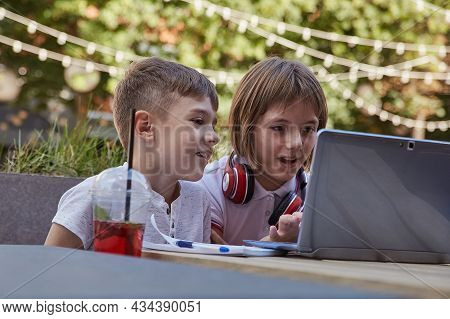 Boy And Girl Sit Outdoors, Watch At Screen Of Laptop. Little Caucasian Schoolchildren Sitting At Tab