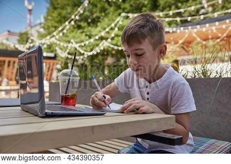 Little Schoolboy Doing Homework Outdoors With Laptop. Caucasian Boy Sitting At Table At Veranda Of C