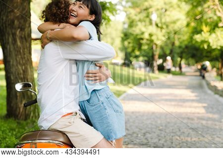 Smiling multiethnic couple hugging sitting on a motorbike in park