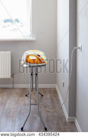 The Electric Iron Is Plugged Into The Socket On The Ironing Board In The Room Against The Background