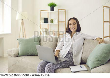 Portrait Of Senior Stylish Female Freelancer Working Remotely Using Laptop And Notepad.
