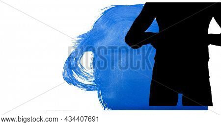 Mid section of silhouette of female handball player against blue paint brush strokes. sports and competition concept