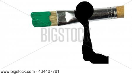 Mid section of silhouette of female handball player against paint brush with green painted tip. sports and competition concept