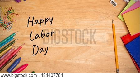 Happy labor day text over multiple school equipment on wooden table. labor day celebration concept