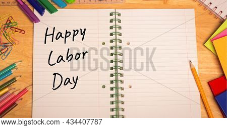 Happy labor day text over open book against multiple school equipment on wooden table. labor day celebration concept