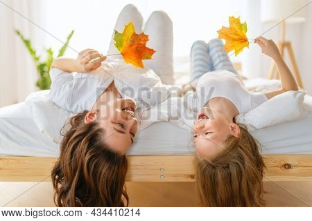 A nice girl and her mother enjoying sunny morning. Good time at home. Child wakes up from sleep. Family playing on the bed in the bedroom.